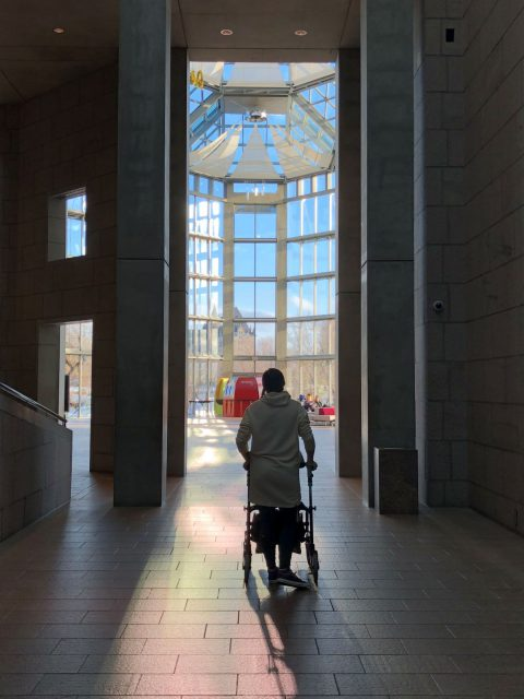 Jasmine is walking away from the camera, using a rolling walker, as she goes down a long corridor into a large glass room with high glass ceilings.