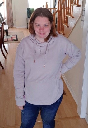Amanda is a white woman with light brown hair.  She is standing in a hallway with her hand on her hip and smiling at the camera.  She is wearing a cream sweatshirt and jeans.