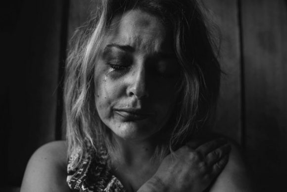 a greyscale photo of a woman crying. Her eyes are closed and tears are on her cheeks.