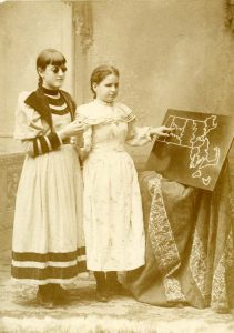 Photo of Edie Thomas a deaf-blind student and her blind friend standing before a propped up map of Massachusetts. Edie points to Hampshire County, 1895. Courtesy, Perkins School for Blind Archives