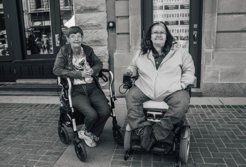 Two women sitting at the side of street