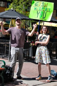 One man and one woman pose for camera while woman holds poster that says CJSW we SUPPORT you
