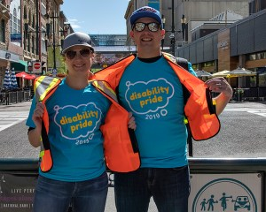 Woman and man in safety vests wearing shirts that say Disability Pride smiling for the camera at a downtown intersection