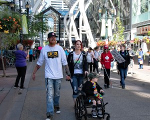 Man and woman holding hands pushing boy in wheelchair