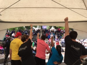 Group of people with hands in air singing