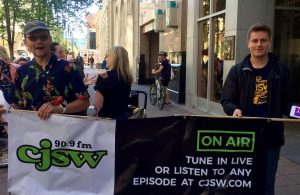 Two men in the street holding banner with the CJSW radio station logo and information
