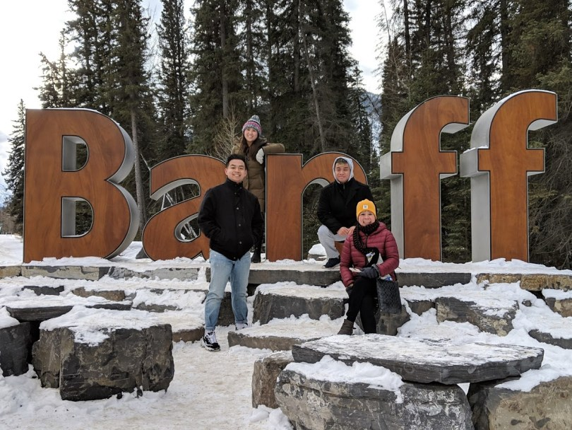 Family smiling and posing together in front of a sign that says Banff