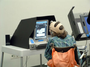 person using a head wand at an accessible voting machine to vote