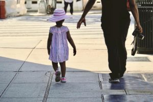 Small girl with matching hat walking with parent on city street.