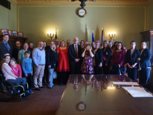 Group standing with Governor Evers for signing of Act 118