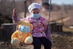 little girl on a swingset with her teddy bear. Both are wearing surgical masks.