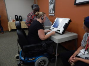 Voter in wheelchair uses accessible voting machine with others looking on