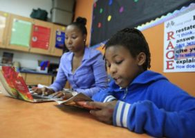 Student at Racine school reading with teacher in background