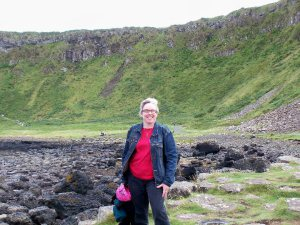 A white woman dressed casually standing at a valley with green hills and black rocks in the background.