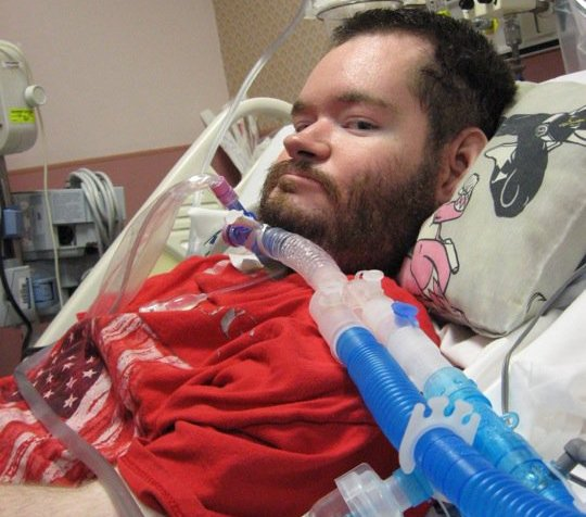 A man with brown hair and a beard sitting upright in a hospital bed. He is using a ventilator.