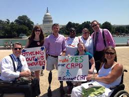 "Photo of 8 people with the Capitol building in the background in Washington, DC. Three people are using wheelchair users. Two people are holding signs that read: ""Nothing about us without us"" and ""Vote Yes for CRPD."""