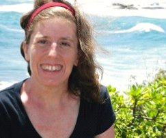 Photo of a white woman smiling at the camera wearing a short-sleeved black t-shirt. The background is the ocean and some green bushes.