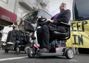 Photo of two people in wheelchairs blocking a bus in San Francisco. In the forefront of the image, a white older woman is sitting in a scooter. On the right, an older white man is in a wheelchair.
