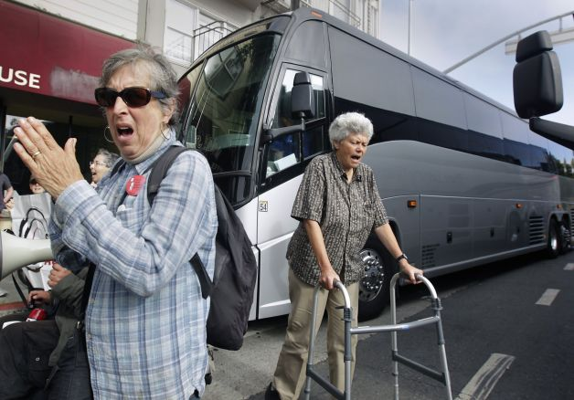 Two older adults blocking a large bus. One older woman is clapping her hand and another woman is using a walker.
