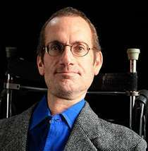 A middle-aged white man with brown hair and glasses. He is sitting in a wheelchair and wearing a dark gray jacket and a blue shirt.