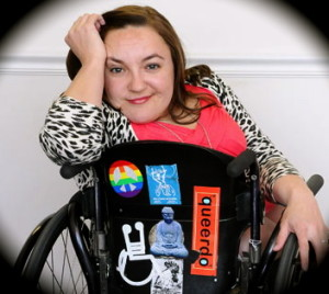 Image of a woman in a wheelchair with her hand cradling her head. She has long brown hair and the back of her wheelchair has various stickers denoting disability and queer culture
