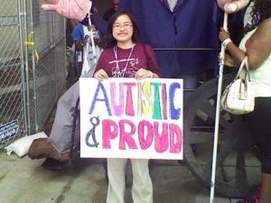 "I am standing in front of several people walking down a stone path, wearing khaki pants and a maroon shirt with the text ""Organizing autistic people..."" visible while holding a large white poster with the colored block letters ""Autistic & Proud"" in marker. I am a light-complexioned Asian female with short black hair cut slightly past my chin, wearing round glasses."