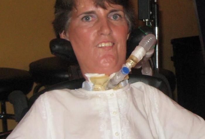 White woman with short brown hair in a wheelchair with a ventilator/trach. She is wearing a white shirt and smiling at the camera.