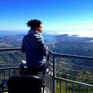 Photo of an Asian American woman standing from her wheelchair overlooking a railing. The background is a blue sky with green hills.