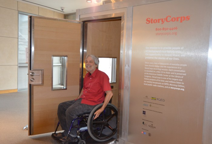 Man in a red short-sleeved shirt in a wheelchair in the doorway of a StoryCorps recording studio