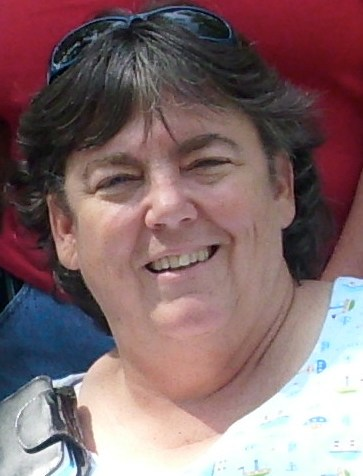 Older white woman with short wavy brown hair. She is wearing a white and blue scoop neck shirt.