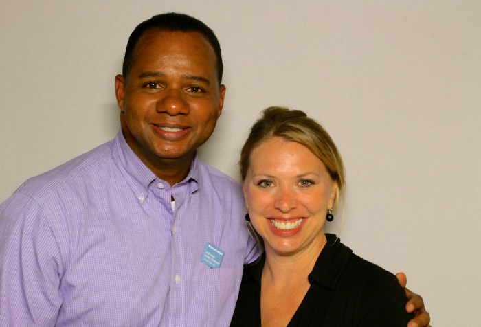 African American man with short hair wearing a light purple shirt. Next to him is a white woman with blonde hair wearing a black shirt. They are both smiling at the camera.