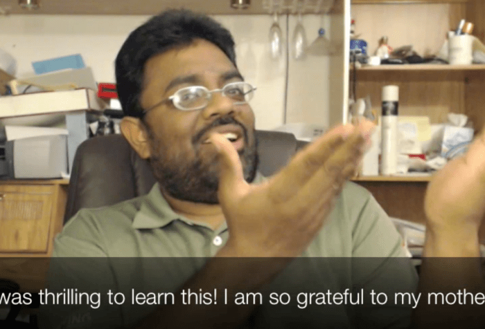 """A South Asian Indian man with glasses and a beard is signing in sign language with his two hands raised. The caption reads: """"It was thrilling to learn this! I am so grateful to my mother!"""""""