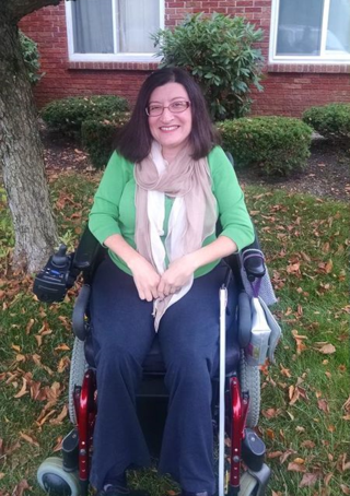 Middle-aged white woman with long brown hair and glasses sitting in a wheelchair outside of her home. She is wearing jeans and a green sweater.
