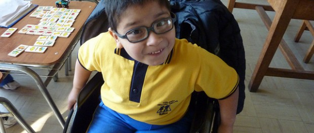Photo of a young boy in a manual wheelchair. He's wearing glasses and a yellow shirt with blue pants.