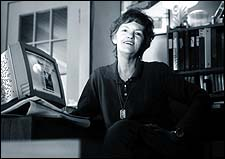 Black and white photo of a white woman with short dark hair. She is wearing a dark shirt and sitting in an office. At the desk is a computer by her side.