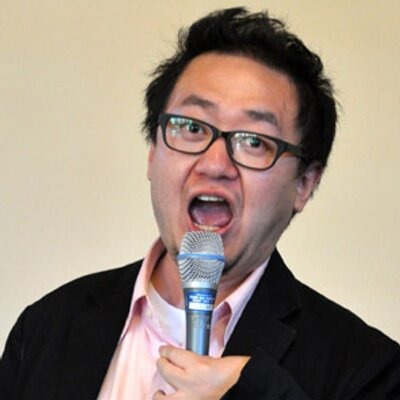 An Asian man with black hair and eyeglasses. He is wearing a black blazer and a pink shirt. His mouth is open wide and he has a microphone near his mouth.