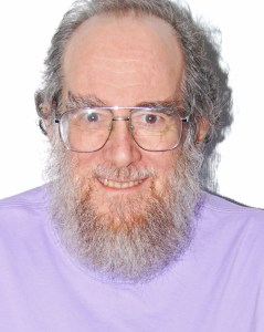 Older white man with gray hair and a long beard. He is wearing glasses and a light purple turtleneck.