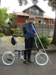 White woman wearing dark sunglasses holding a white cane. She is standing outside of a house and holding a bike.