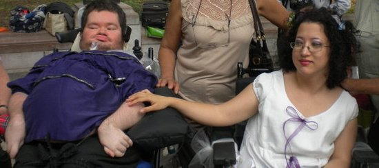 Photo of a man using a ventilator wearing a put;poe t-shirt on the left side. On the right is a woman with dark curly hair wearing glasses and a white dress. She is seated and has her hand touching her husband's arm