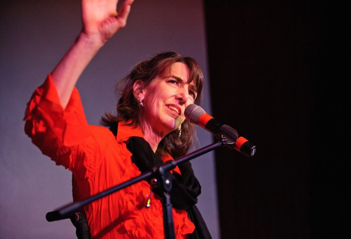 A white woman in a red shirt standing in front of a microphone. Her hand is in the air and looking at something upward.