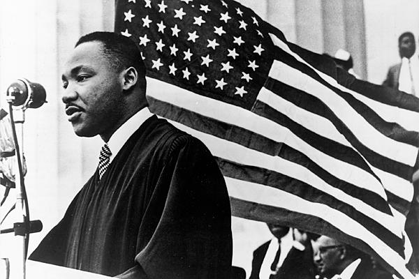 A black-and-white image of an African-American man speaking at a lectern. He is facing a crowd and standing in front of a large American flag.
