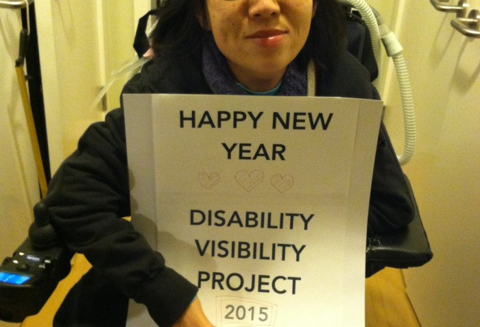 """Image of an Asian-American woman in a wheelchair. She is holding a sign that reads: """"HAPPY NEW YEAR"""" below that are 3 hearts and the text: """"Disability Visibility Project 2015"""""""