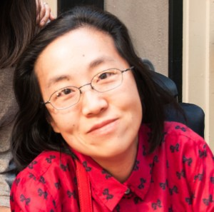 Asian American woman with long black hair and glasses. Her head is tilted slightly to the left side of the photo. She is wearing a red shirt with bows.
