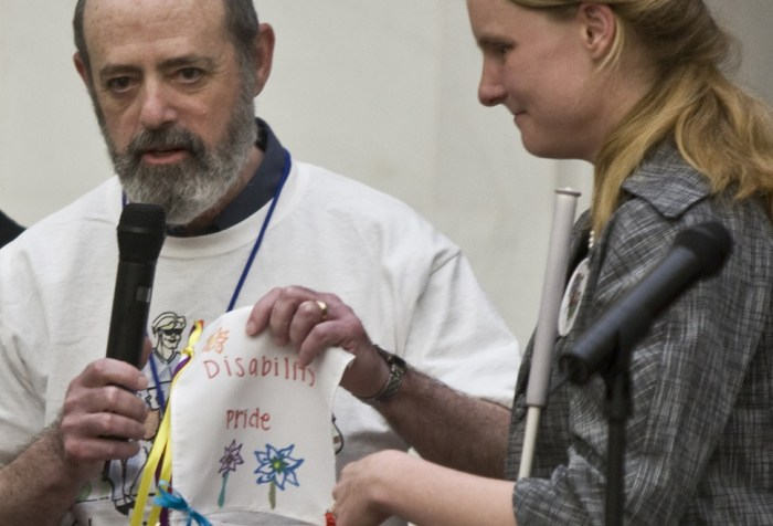 Photo of an older white man who is bald with a beard holding a microphone. He is holding a drawing that has flowers and the words 'Disability Pride.' Next to him is a young woman with long blond hair and a white cane. She is also holding a drawing up.