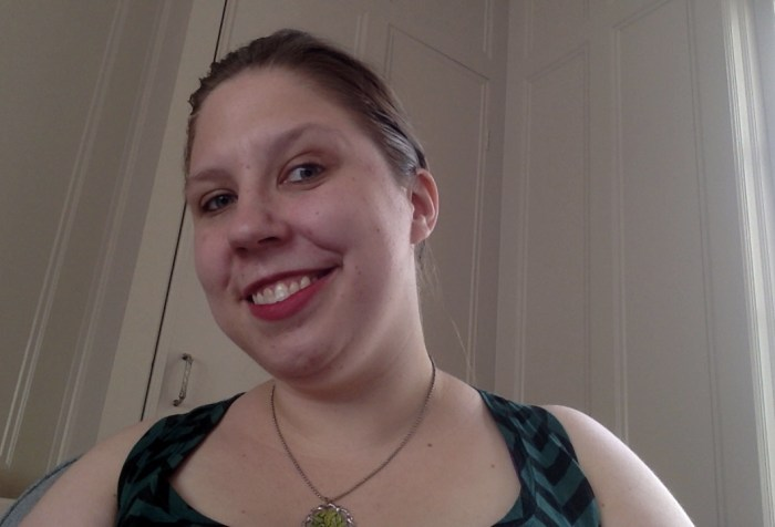 Young white woman smiling at the camera. Her hair is pulled back and she is wearing a tank top and a necklace.