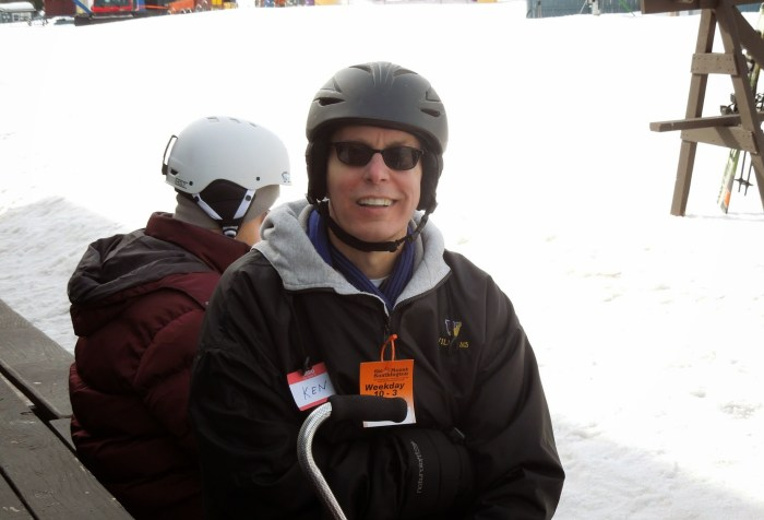 White man in a black ski jacket. He is wearing a helmet against a snowy background. Another person in a helmet is sitting behind him.