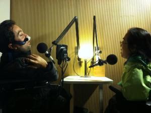 Image of two people in a recording booth with microphones angled near their faces. On the left is a Latino man in a wheelchair using a nasal mask for respiratory support. On the right is an Asian woman in a wheelchair with glasses. They are in conversation with one another.