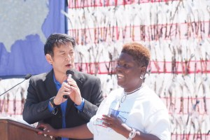 Lois Curis, an African American woman, on stage. She is wearing a white t-shirt and behind her is a large flag of the United States. An Asian American man is standing next to her with a microphone