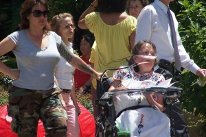 Laura Hershey, a white woman in a wheelchair with a mouthstick and nasal mask in a wheelchair. She is wearing a white sundress with flowers. At her left is her personal assistant standing by her side, with her hand on the wheelchair.
