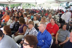 A large number of people sitting in folding chairs under a tent.
